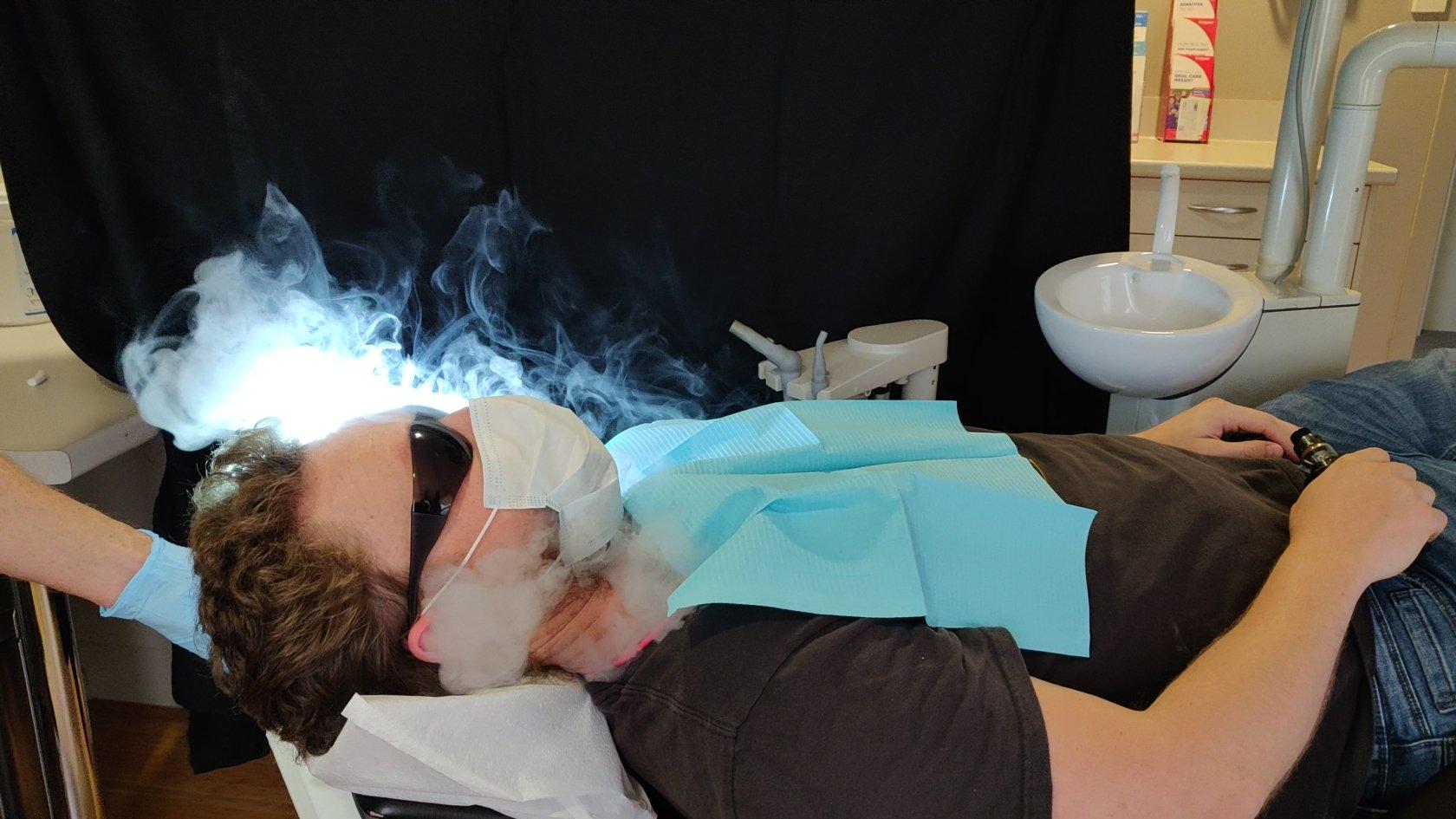 A patient breathes out vape in a mask to show aerosol escape